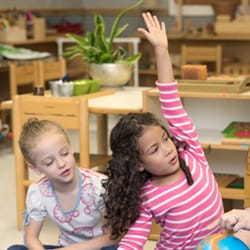 Una niña levantando su mano