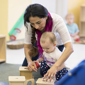 Infant and teacher play with blocks