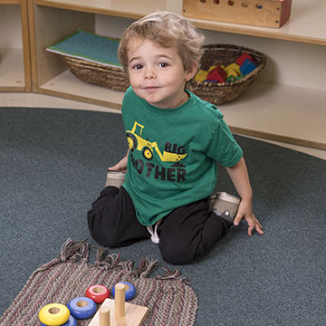 Toddler boy kneeling with toys